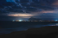 The coastline of Denia shined by moonlight seen from the beach of Daimus, Spain