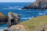 KYNANCE COVE CORNWALL, UK - MAY 14 : People admiring the rugged coastal scenery at Kynance Cove in Cornwall on May 14, 2021. Two unidentified people