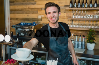 Portrait of smiling waiter offering cup of coffee at counter