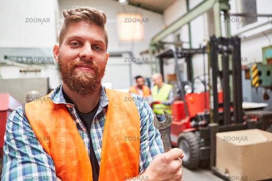 Mann als stolzer Lagerarbeiter mit Schraubenschlüssel