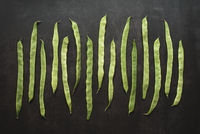 Top view of whole green beans in a row on dark background