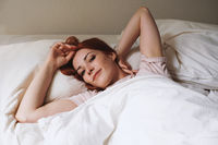 happy smiling young woman lying in bed after waking up