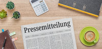 A newspaper on a desk with the headline Press Release in german - Pressemitteilung