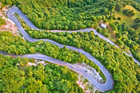 Curvy road serpentines in green Alpine ladscape aerial view, Agueglio Pass mountain road above Varenna