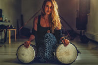 beautiful young girl playing on djembe.