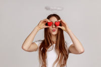 Woman covers eyes with toy hearts as if looking with love, sending air kiss, affection in relations.