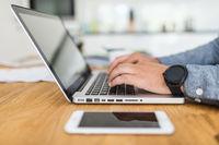 Closeup on man using his laptop at home