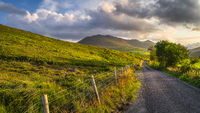 Country road leading toward Carrauntoohil mountain in MacGillycuddys Reeks mountains at sunset
