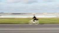 Woman cyclist in motion on a straight asphalt road