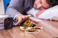 Young male employee in oversleeping concept