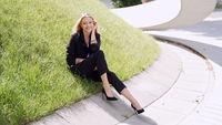 Positive businesswoman sitting on grass