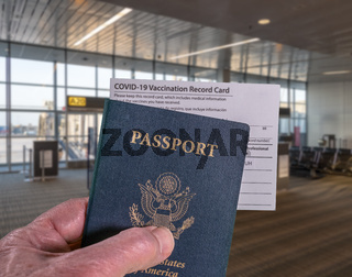 Concept of Covid-19 vaccination record certificate and US passport to show immunity to virus at airport