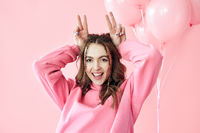 Young pretty woman have fun showing horns with fingers over head on pink background