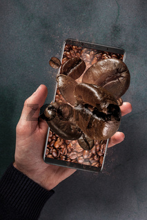 Fresh roasted coffee beans and mobile phone concept