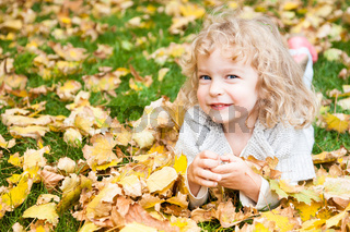 Child lying on yellow leaves