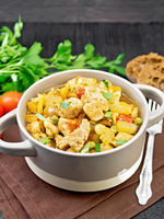 Chicken with vegetables and peas in saucepan on black board