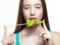 Teenager girl licking the lollipop. Sweet tooth concept