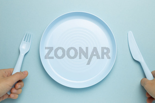 Fork, knife and empty plate on sky blue background. flat lay, top view, copy space