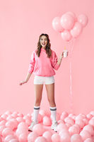 Full length portrait of trendy young woman with milk shake over pink balloons background