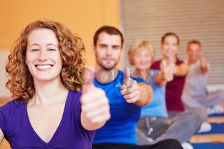 Frau im Fitnesskurs hält Daumen hoch