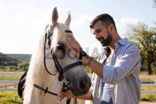 The happy man is stroking a white horse in a ranch