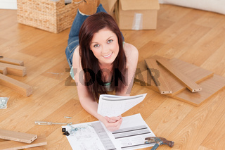 Pretty red-haired girl posing while reading a manual before do-it-yourself