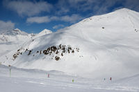 Skiers and snowboarders downhill on freeride trace and mountains with clouds at sun cold day