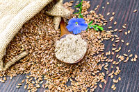 Flour flax in spoon with seeds and flower on board