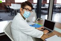 Asian male doctor wearing face mask sitting at desk in hospital office using laptop