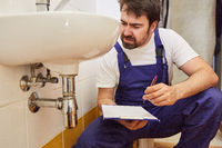 Klempner mit Checkliste nach Reparatur am Siphon