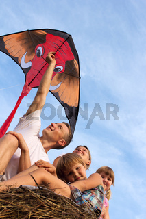 Family from four people against the blue sky flying kite.