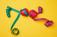 red heart and green measuring tape on yellow background