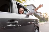 happy smiling woman or female passenger in car