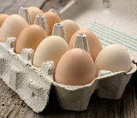 fresh whole brown eggs in paper packaging on a gray wooden background