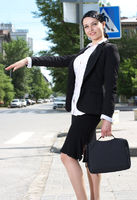 Beautiful youn business woman hailing taxi cab