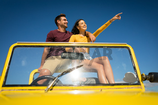 Happy caucasian couple sitting in beach buggy by the sea pointing