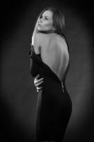 Beautiful slim woman undressing dark dress.