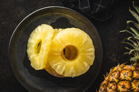 Canned sliced pineapple fruit on plate.