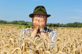 nachdenklicher Landwirt in einem Getreidefeld