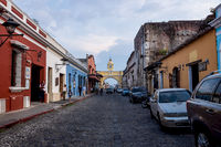 Tourists walking along the cobbled streets and along the Gate 'Arco de Santa Catalina' of the colonial town Antigua, Guatemala