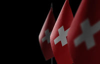 Small national flags of the Switzerland on a black background