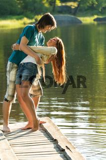 Playful couple having fun on pier lake