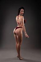 Muscular female in bikini show perfect back looking at camera