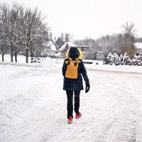 Eine Frau läuft im Winter auf der Fahrbahn einer Straße
