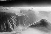 Black and white high snowy mountains covered with beautiful clouds and fog in snowfall