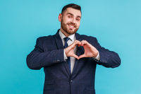 Happy handsome bearded man wearing official style suit standing with heart or love gesture and looking at camera with toothy smile.