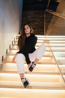 Young beautiful brunette fashion model posing on stairs.