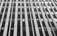 close up perspective detail of tall high rise brutalist style office building with white vertical concrete lines and dark windows