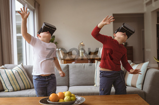 Two caucasian boys wearing vr headsets gesturing in the living room at home