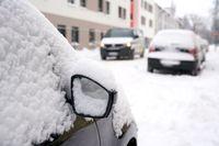 eingeschneite Autos in einer Straße im Winter